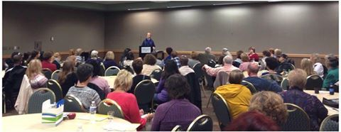 Photo of Lev Raphael speaking to a room of 100 people in 2014