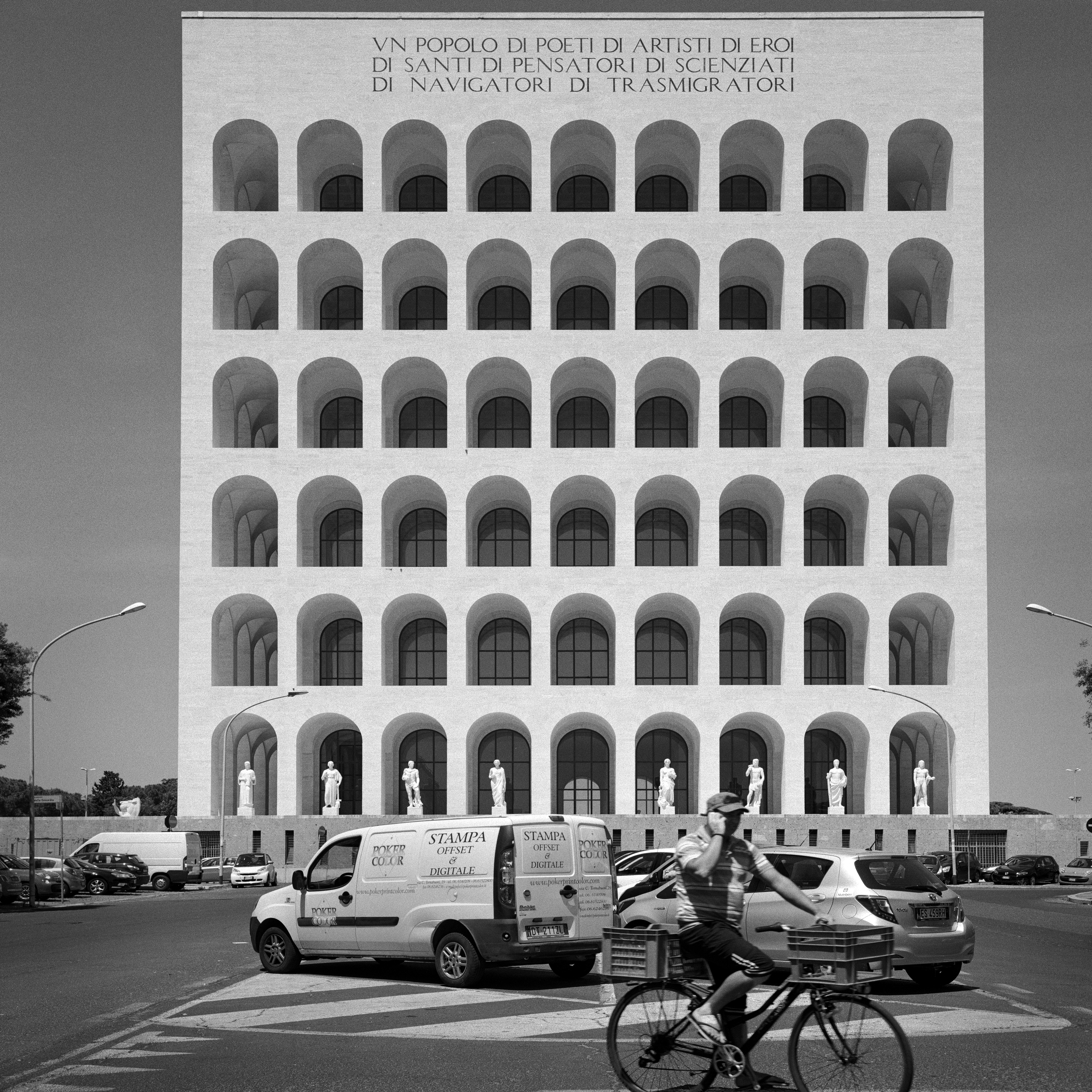black and white image of a building in Rome with arched windows. A car park in the foreground, a man on a bicycle appears to be talking on the phone
